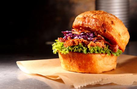 nosh: Rustic Pulled Pork Burger on a metallic countertop fot burger restaurant concepts