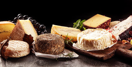 Food Still Life - Variety of Aged Cheeses Spread Out Dark Table in front of Black Background with Copy Space Reklamní fotografie - 49117964