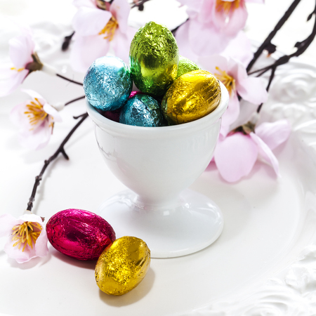 egg cup: Colorful foil wrapped Easter eggs in a ceramic egg cup with dainty pink spring blossom for a festive Easter holiday background, high angle view Stock Photo