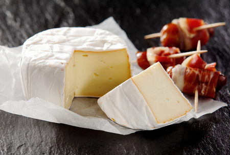 wedge: Close Up of Soft Aged Cheese Round with Cut Wedge on Dark Rough Textured Surface with Cured Meat Appetizers on Toothpicks