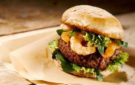 gourmet kitchen: Gourmet shrimp and beef burger with whole fresh grilled shrimp on a juicy beef patty with lettuce, close up view on brown paper in a rustic kitchen or restaurant Stock Photo