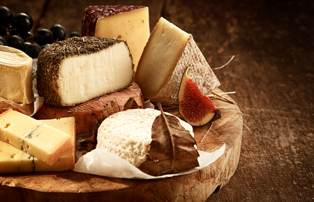 gourmet: Close Up of Gourmet Cheese Tray Served on Wooden Board - Variety of Cheeses on Rustic Wood Table with Fruit Garnish and Copy Space Stock Photo