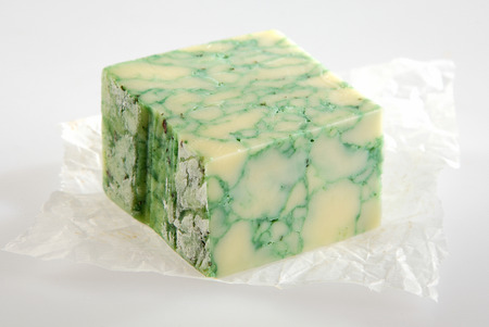 speciality: Portion of delicious speciality sage cheese with a distinctive mottled green pattern from the herb displayed on crumpled white paper over a white background, close up high angle view