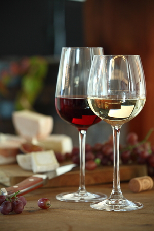 skoal: Two elegant glasses of red and white wine served with assorted cheese on a platter , shallow DOF and dark rustic background Stock Photo