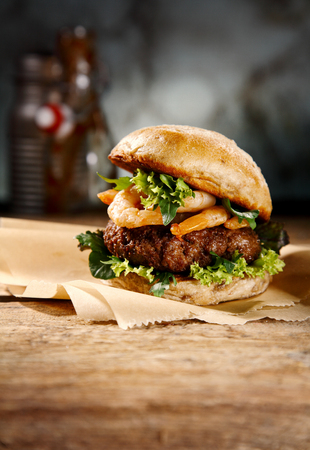 Speciality seafood and beef burger with grilled prawns and a juicy beef patty on lettuce served on a rustic counter for a pub lunch