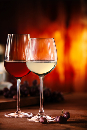 skoal: Two glasses of red and white wine on a wooden table in front of a blazing fire with selective focus to the glasses of beverage Stock Photo