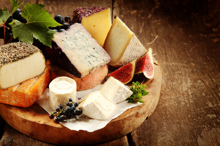 speciality: Gourmet cheese platter with fresh figs and grapes amongst an assortment of speciality soft and semi-hard cheeses on a rustic wooden table, close up high angle view
