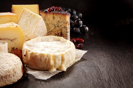 Close Up Still Life of Variety of Gourmet Cheeses with Soft Melting Cheese Round in Foreground with Fruit Garnish on Dark Rough Textured Background with Copy Space
