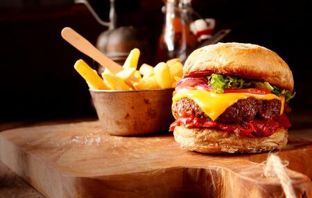 papas fritas: Caliente con queso guindilla con salsa de chile picante, una hamburguesa de ternera y queso derretido servido con una guarnición de patatas fritas crujientes en una tabla de madera en el restaurante rústico Foto de archivo