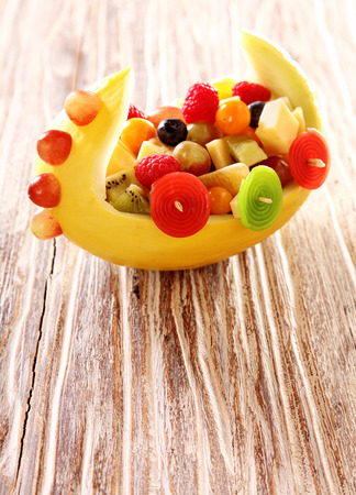 salad decoration: Colorful healthy fresh fruit salad in a melon boat as a decoration for a kids party on a textured wood table with distinctive woodgrain and copyspace Stock Photo