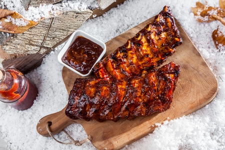 spare ribs: Two portions of grilled spicy spare ribs cooked on a winter barbecue served outdoors in the snow on a wooden board with savory sauce