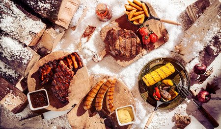 wedges: Seasonal winter barbecue in snow with grilled spicy steak, ribs and sausages served with assorted grilled vegetables and potato wedges, overhead view