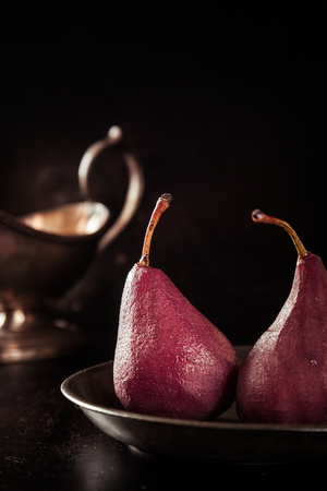 shadowed: Glazed fresh whole pears steeped in red wine served for a speciality dessert with a silver sauce boat alongside in a dark shadowed environment Stock Photo