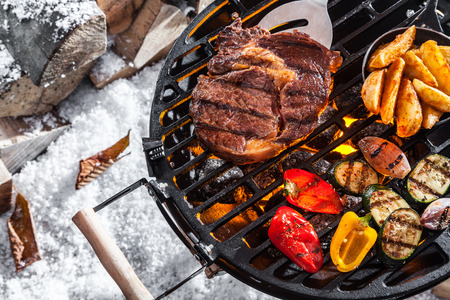 aerial view: Outdoors winter barbecue with marinated meat and fresh healthy vegetables grilling over the hot coals on a portable BBQ, high angle on snow
