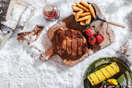 ribeye: Winter BBQ with spicy marinated rib-eye steak and vegetables including corn and potato wedges served on rustic platters outdoors in snow