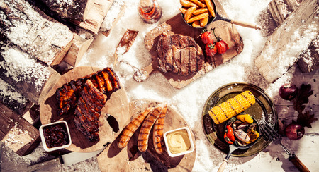 Delicious winter barbecue spread with assorted grilled marinated meat and vegetables served outdoors in the snow, overhead view Stock Photo