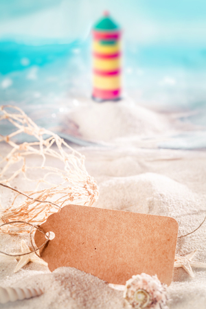 sea fan: Summer holidays at the seaside concept with a blank brown gift tag nestling in beach sand with seashells and a sea fan with a blurred lighthouse and ocean in the background