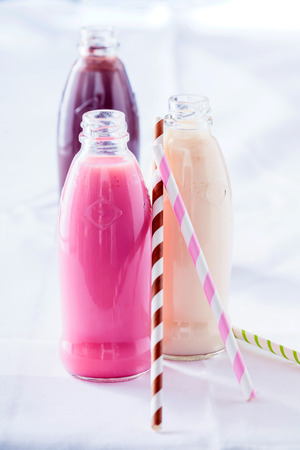 tropical drink: Some delicious milkshakes with strawberry, choc and vanilla flavour on white background or table Stock Photo