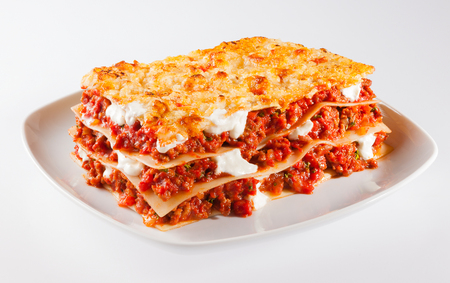 carbohydrates: Tasty serving of traditional Italian lasagne with spicy tomato based ground beef and melted mozzarella cheese between layers of noodles Stock Photo