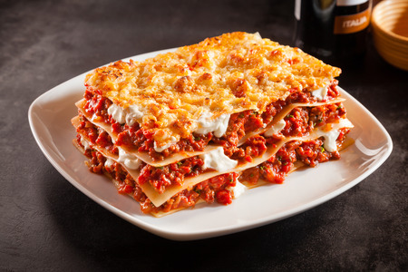 a traditional: Tomato and ground beef lasagne with cheese layered between sheets of traditional Italian pasta served on a white plate on a dark restaurant or bar counter