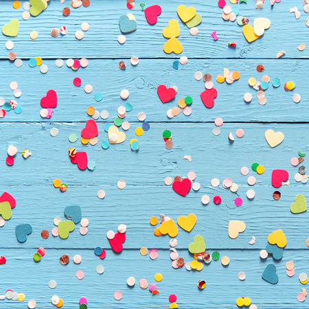 fasching: Background of blue painted wooden wall with colorful pink, red, yellow and green heart and circle confetti Stock Photo