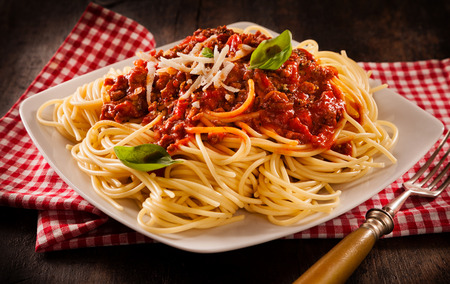 Rustic serving of traditional Italian spaghetti Bolognese topped with fresh basil and grated cheese on a modern square white plate and checkered re and white napkin Stock Photo