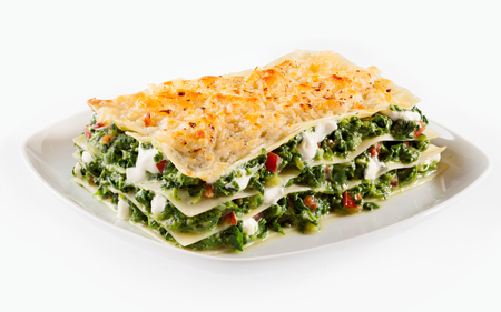 baby spinach: Baby spinach lasagne with mozzarella alternating with layers of traditional Italian noodles served on a square plate isolated on white
