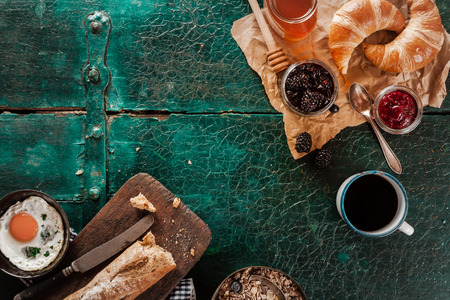 top angle: Breakfast spread with coffee, bread, fresh croissants, fried egg, honey and preserves on an old rustic green wooden table, overhead view with copyspace