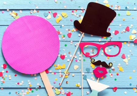 Party-Spaß mit Photo Booth Zubehör als gent in einem Zylinder angeordnet mit einem Schnurrbart Cocktails mit einem magentafarbenen Kreis mit Kopie Raum neben für die Einladung oder Gruß nippen