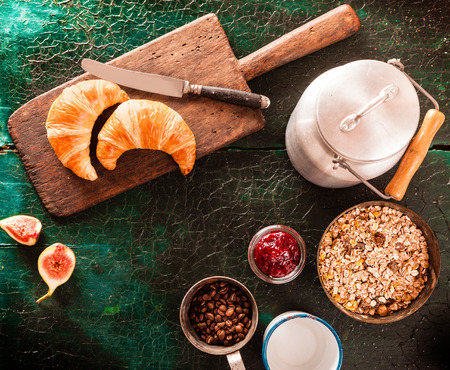 break fast: Rustic or country breakfast with muesli, milk in a can, fresh figs and fresh croissants on a bread board, overhead view on green boards with copy space