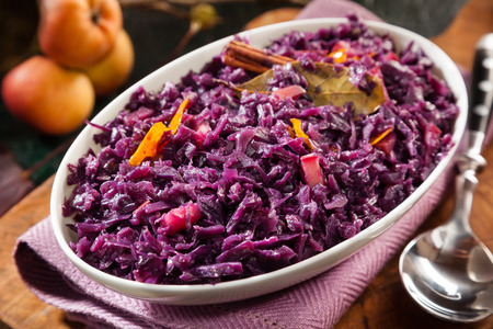accompaniment: Tasty recipe for braised red cabbage and apple seasoned with bay leaves served in an oval dish on a napkin for a tasty vegetarian diet or accompaniment to a meal Stock Photo