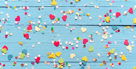 scattered: Colorful party confetti, some heart-shaped, on a rustic blue wood background scattered randomly across the surface, wide angle view