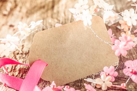 古い風化した木のバック グラウンドにピンクと白の可憐な春花に囲まれたピンクのお祝いリボンで結ばれた空白の素朴な茶色ギフト タグ