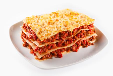 Pikante Hackfleisch oder Hackfleisch-Lasagne mit Blättern der traditionellen italienischen Nudeln mit leckeren Fleisch abwechselnd auf einem Teller serviert isoliert auf weiß