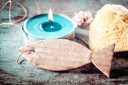 Turquoise Tea candle light, sponge and Tag on rustic blue background for maritime concepts.