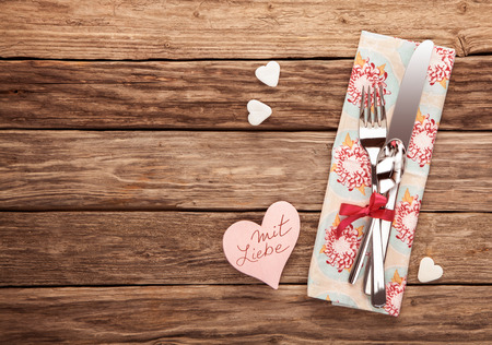 in liebe: Mit Liebe on Valentines Day or anniversary written on a pink paper heart alongside a romantic place setting with a napkin and silverware tied with a red ribbon, overhead view on wood with copy space