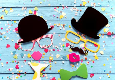 Party machen mit Fotokabine Personen bestehend aus bunten Accessoires mit einem gent und Dame in Top-Hüte und Sonnenbrillen schlürfen Cocktails Urlaub umgeben von Konfetti auf einem blauen Hintergrund Holz