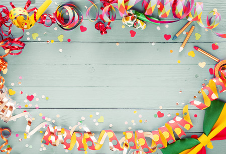 Colorful party frame with streamers and confetti and a vibrant bow tie in a corner around central copy space on a rustic wooden background