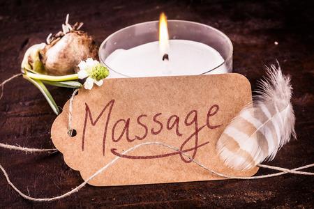Spa massage concept met een handgeschreven bruin tag, het branden van aromatische kaars, ontspruit voorjaar bol en vogel veer in een close-up stilleven Stockfoto