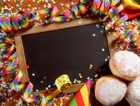 twirled: Party border or frame with cookies and colorful paper confetti surrounding a blank vintage school slate with twirled streamers, copy space for your festive greeting, overhead view