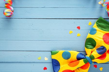 Kleurrijke polka dot partij vlinderdas en verspreid confetti op rustieke blauwe houten planken met kopie ruimte voor uw groet of uitnodiging, bovenaanzicht