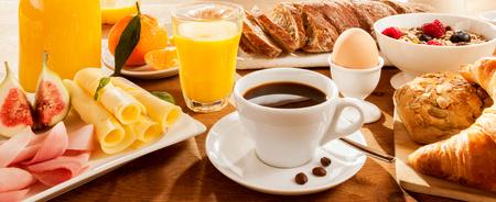 Uitgebreid ontbijt met vijgen, eieren, vlees, brood, koffie en sap Stockfoto
