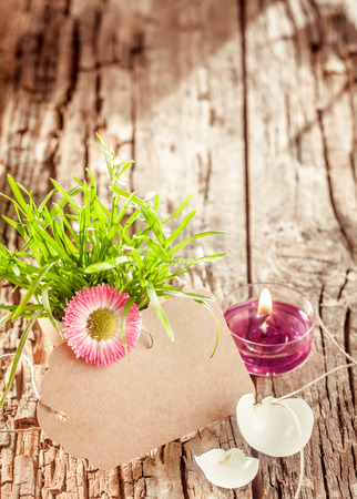 eggshell: easter grass and eggshell and blank tag with copy space and candle on rustic wooden background for your individual concept design.