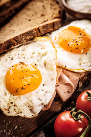 고추와 양념이 기름에 튀긴 된 계란 맛있는 계란, 햄, 토마토 아침 식사는 건강한 갈색 곡물 빵과 봉사