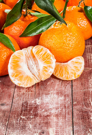 clementine fruit: Delicious fresh peeled tangerine, clementine or mandarin displayed together with the whole fruit on a rustic wooden table with copy space
