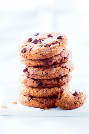 chocolate cookies: Stack of crunchy chocolate chip cookies with the remnants of an eaten or broken one alongside on a textured white background with copy space