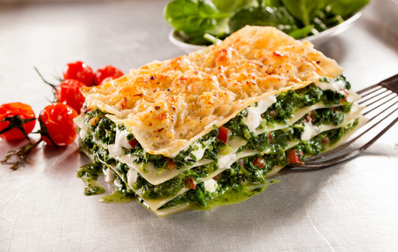 lunch meal: Healthy spinach and cheese Italian lasagne topped with crispy cheese with roasted tomatoes served on a spatula for a tasty lunch or meal Stock Photo