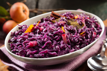 Dish of braised red cabbage and apple for a delicious savory accompaniment flavored with dried bay leaves and seasoning