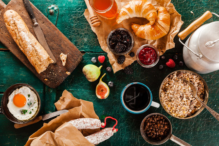 jams: Wholesome rustic breakfast with cereal, fried egg, bread, jams, sausage, milk in a can and coffee spread out on a green wooden background, overhead view