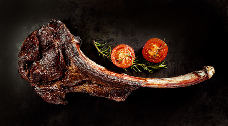 Succulent grilled tomahawk beef steak on the bone with fresh rosemary and a cherry tomato on a black background viewed from above